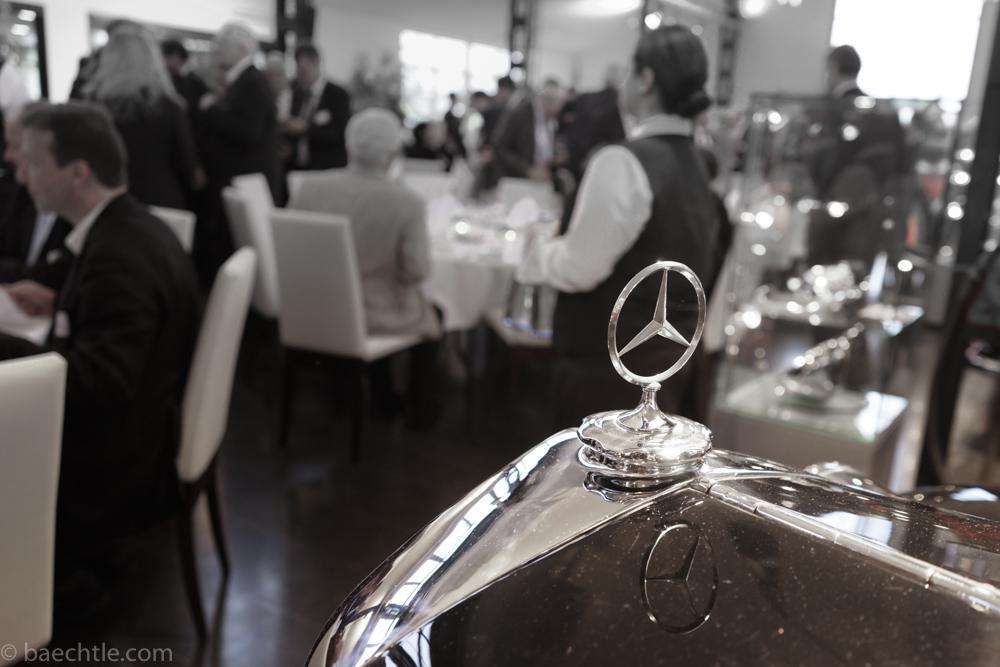 Im Vordergrund ist der Mercedes-Stern eines Oldtimers zu sehen. Dahinter sind Menschen bei einer Veranstaltung.