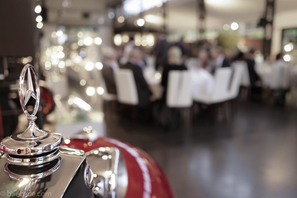 Eventfoto: Ein Mercedes Oldtimer im Vordergrund, dahinter stehen Tische einer Gala-Veranstaltung