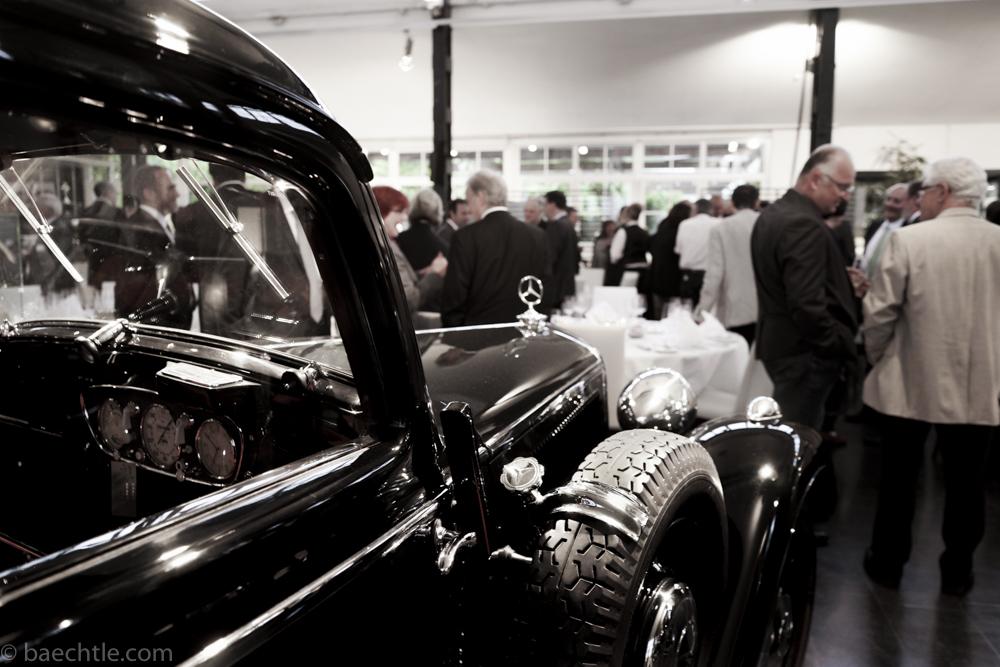 Im Vordergrund steht ein Mercedes Oldtimer, dahinter ist eine Gruppe Menschen bei einer Gala-Veranstaötung