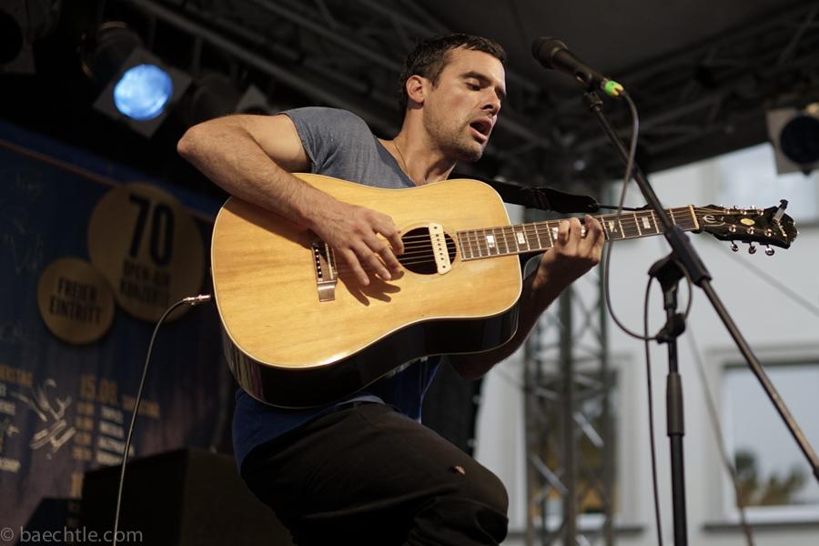 Ein Mann spielt Gitarre und singt in ein Mikrofon.