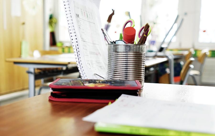 Auf einem Tisch in einem Klassenzimmer liegt ein Mäppchen. Dahinter steht eine Blechdose mit einer Schere, einem Klebestift und anderen Arbeitsmitteln.
