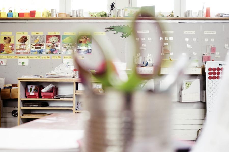 Blick in ein Klassenzimmer einer Grndschule. Im Vordergrund steht eine Blechdose mit einer Schere