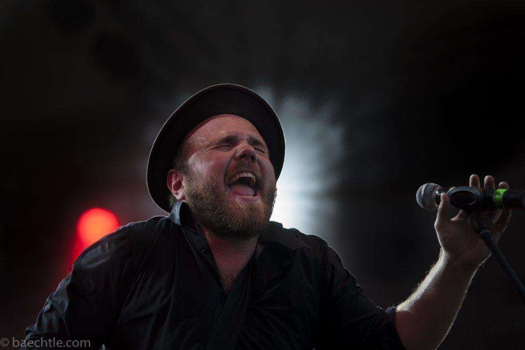 Fotografie beim Konzert: Ein bärtiger Mann mit Hut singt