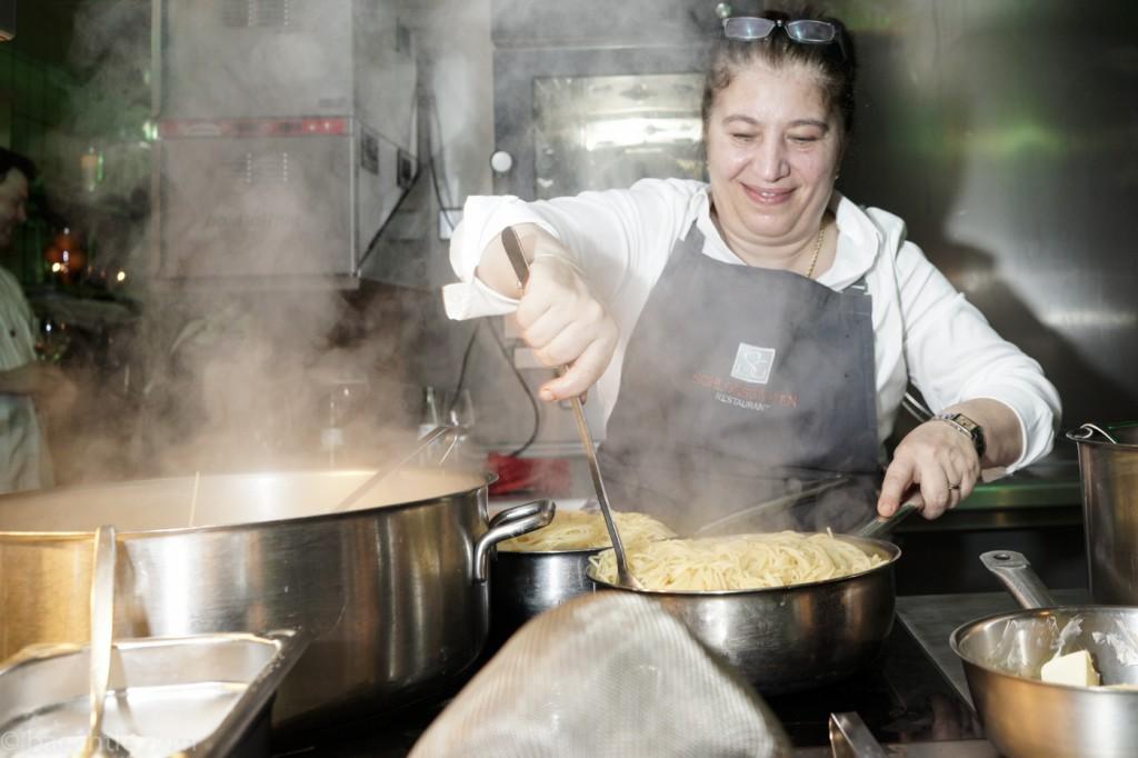 Eventfotografie in der Küche: Eine Köchin holt Spaghetti aus einem Topf