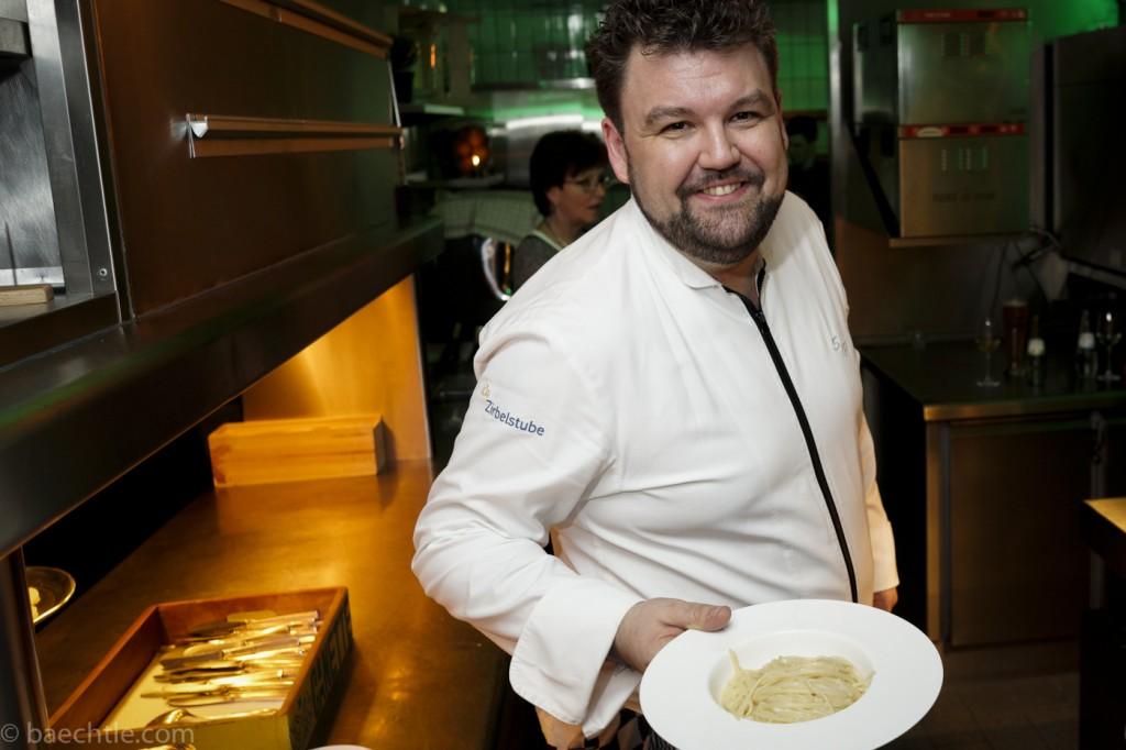 Ein Koch in einer weißen Kochjacke hält einen Teller Spaghetti in der Hand und lacht in die Kamera.