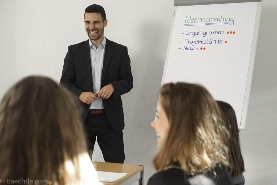 Fotografie bei einer Besprechung im Büro: Ein Mann steht lachend neben einem Flipchart. Im Vordergrund sitzen zwei Frauen.