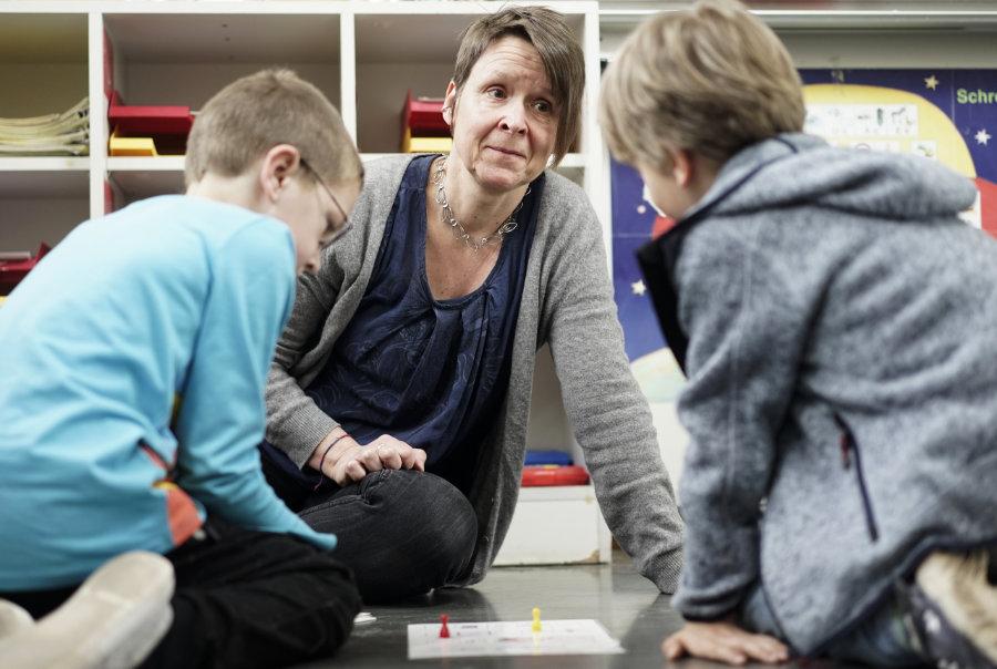 Fotografie in der Schule: Eine Lehrerin sitzt auf dem Boden vor zwei Schülern.