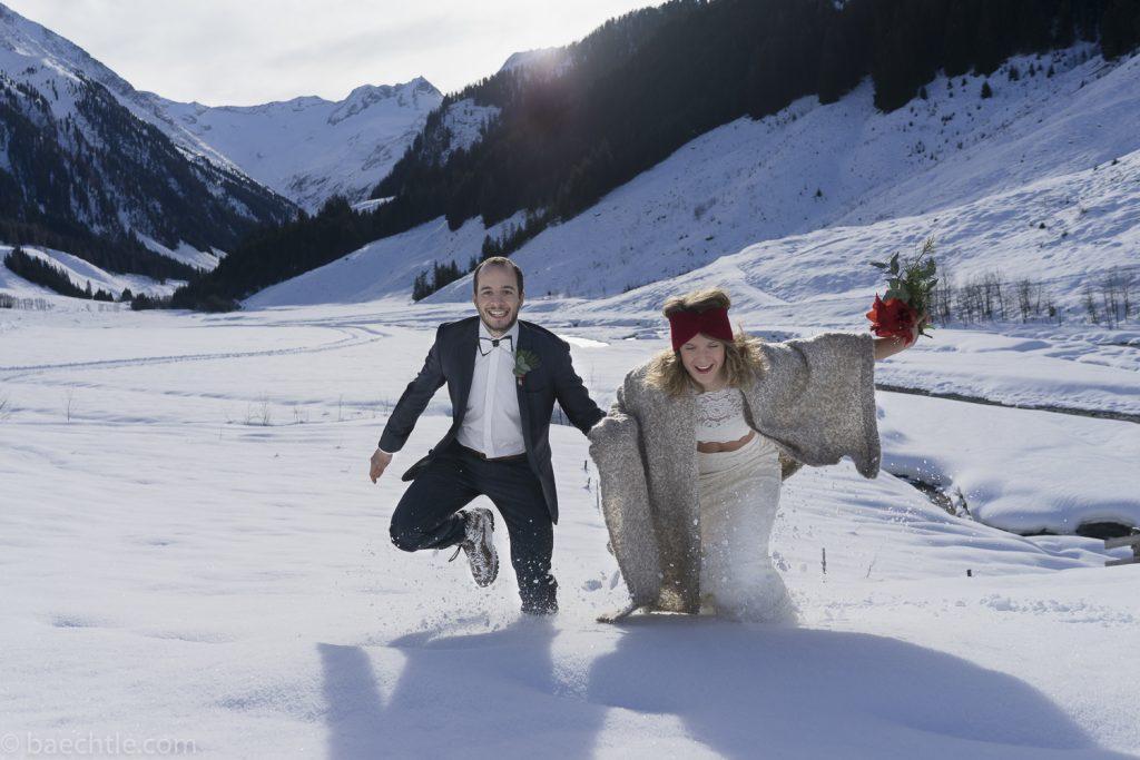 Fotografie bei einer Hochzeit: Brautpaar rennt im Schnee