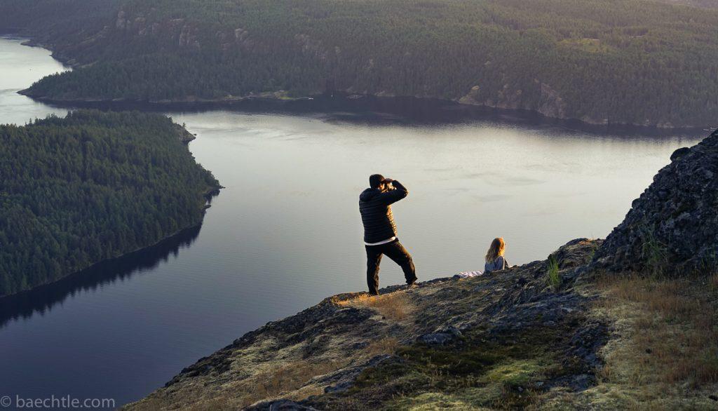 Fotografie auf Reisen: Ein Mann steht uf einem Felsen und fotografiert.