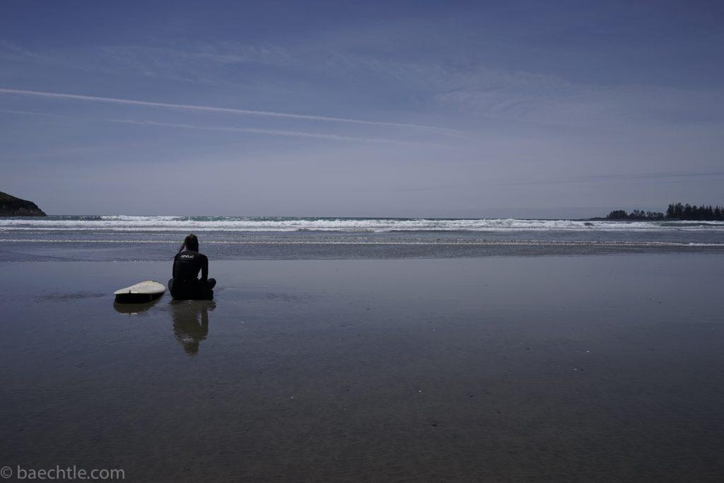 Fotografie beim Sport: Eine Surferin sitzt am Strand im Wasser.
