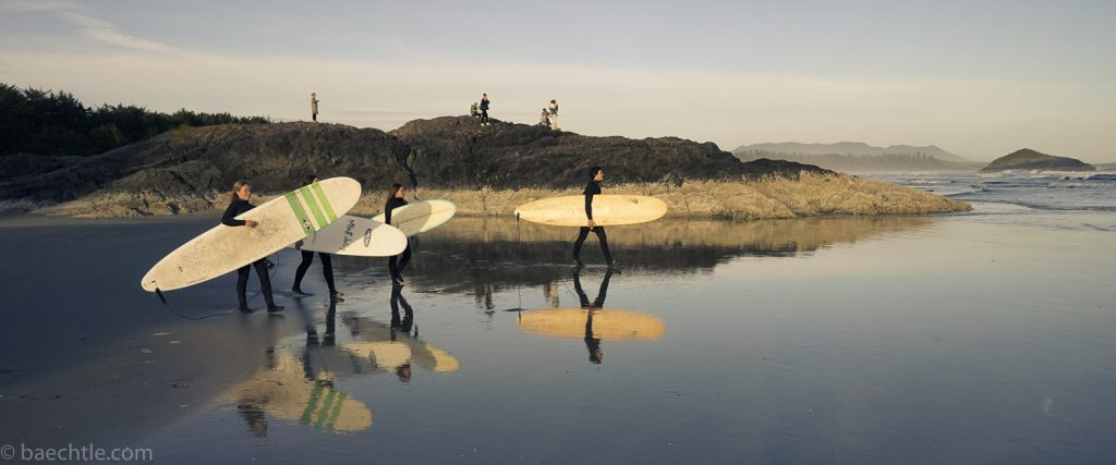 Fotografie am Strand: Vier Surfer gehen mit ihren Surfbrettern ins Wasser