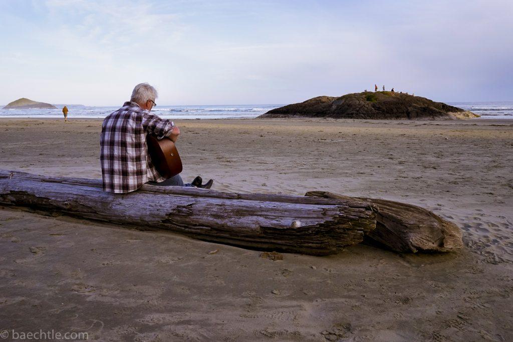 Fotografie: Ein Mann sitzt am Strand auf einem Baumstamm und spielt Gitarre.